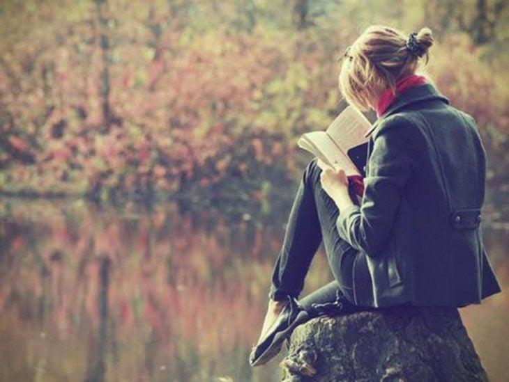 chica leyendo en una piedra