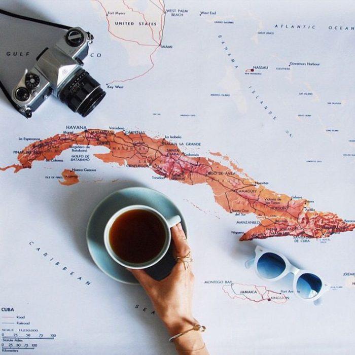 mano de una chica con una taza y cámara sobre un mapa
