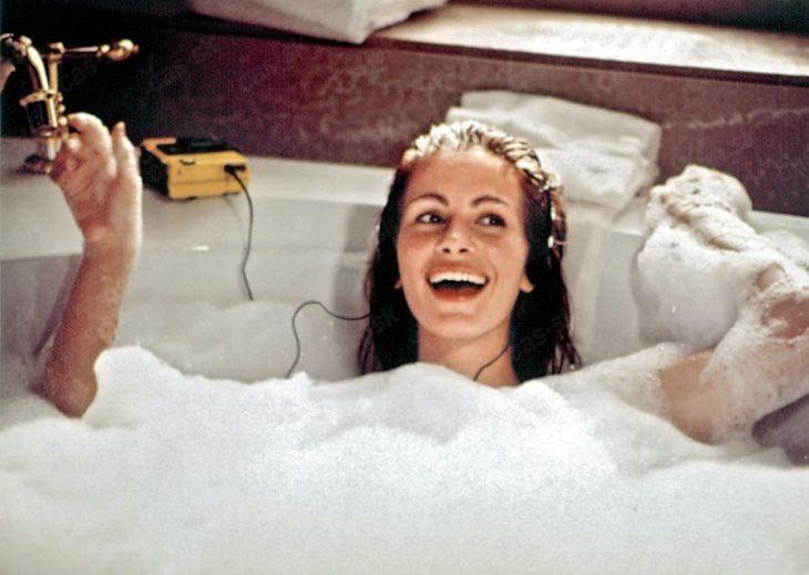chica en baño de tina con audífonos sonriendo