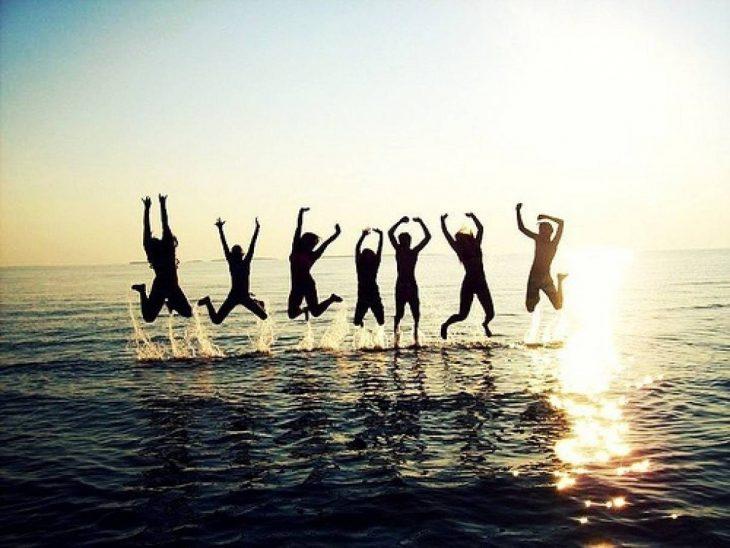 amigos en la playa brincando en el mar