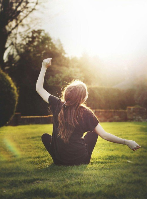 chica sentada en pasto contenta