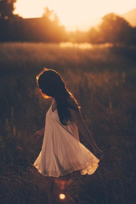 chica caminado en el campo al atardecer