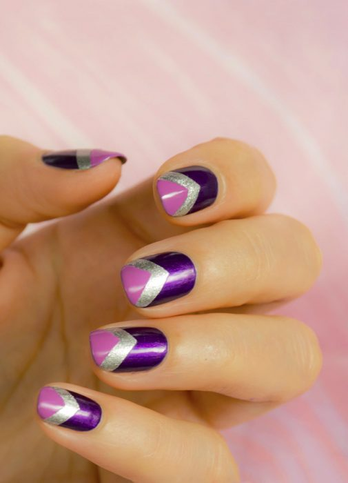 Diseño de uñas de color morado con franjas plateadas y rosas