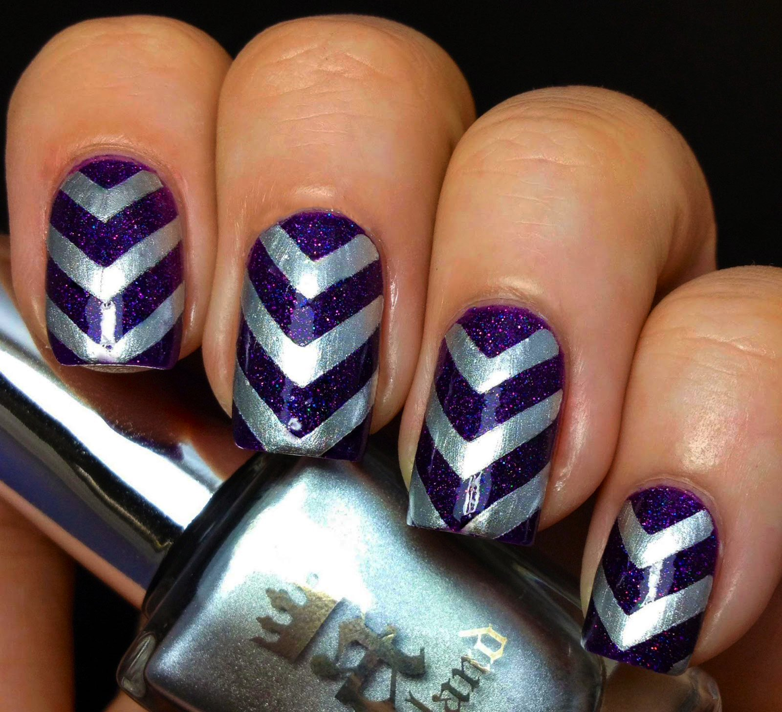 Diseño de uñas color morado con lineas color plateado