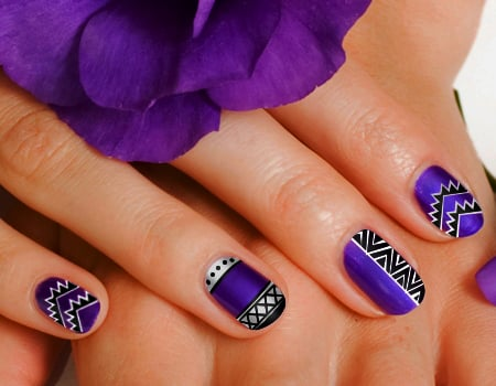 Diseño de uñas color morado con dibujos tribiales