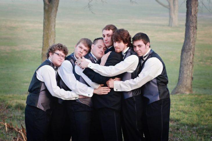 padrinos de boda abrazando al novio
