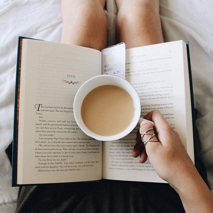 Chica tomando una foto a su café mientras lee un libro