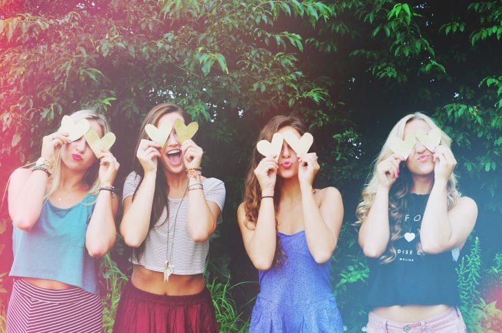 Chicas posando con corazones de papel en sus ojos para una fotografía
