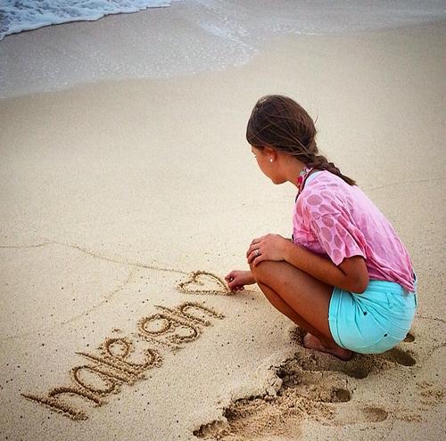 Chica escribiendo su nombre en la arena