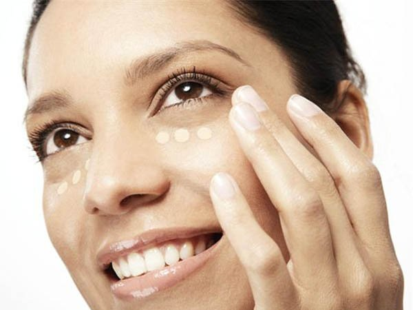 mujer aplicando corrector facial