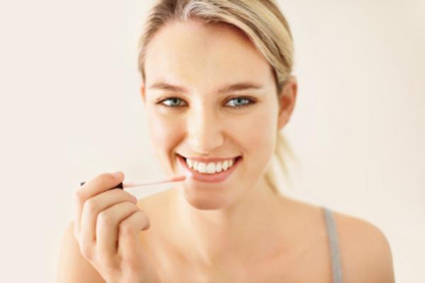 mujer aplica brillo labial