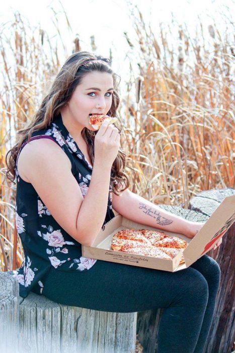 Chica sentada comiendo pizza