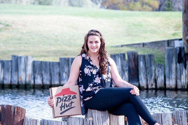 Chica sentada en un parque comiendo pizza