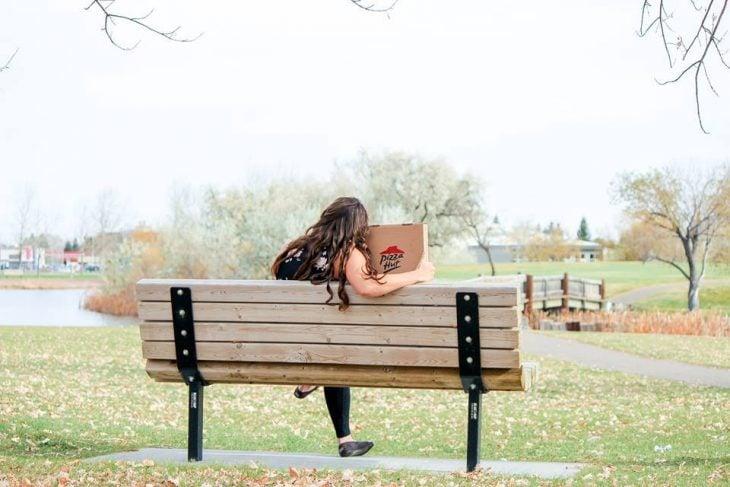 Chica sentada junto a una caja de pizza