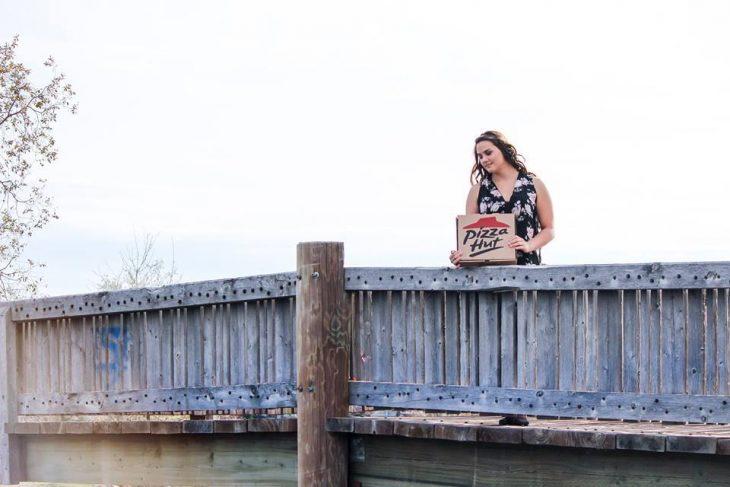 Chica paseando por un puente mientras carga una caja de pizza
