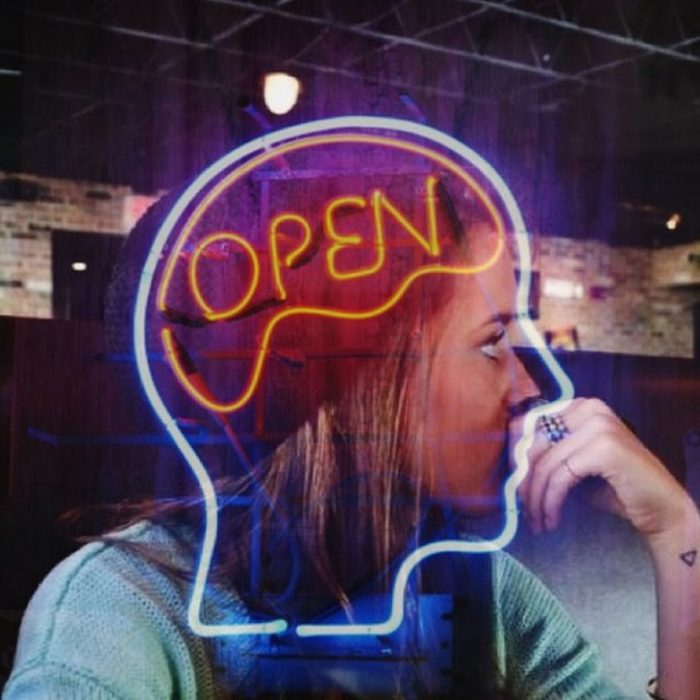 mujer frente letrero neon