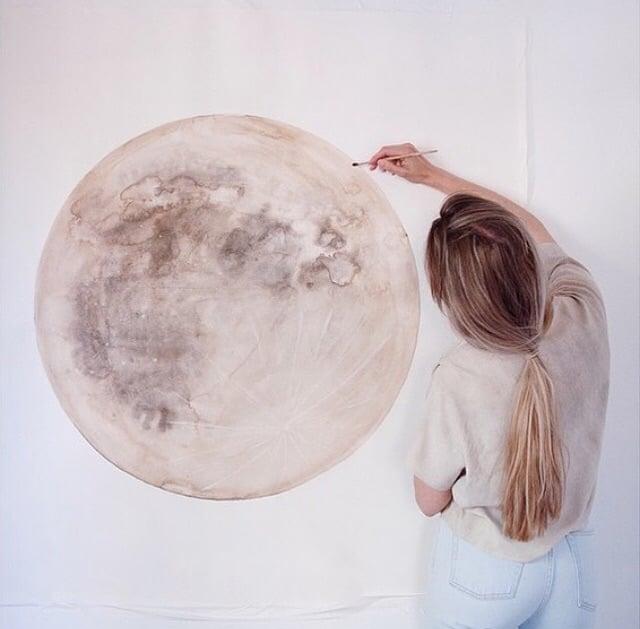 chica dibujando una luna en la pared