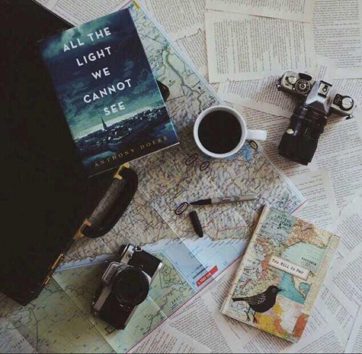 escritorio con tasa, mapas libros y café