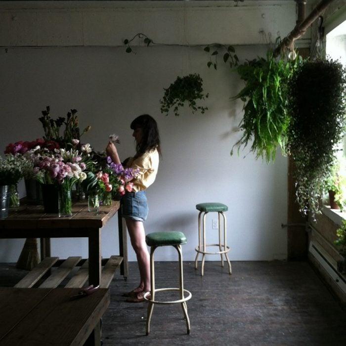chica acomodando flores