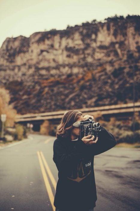 chica tomando fotos en carretera
