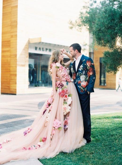 Vestido de novia de color melón con diseños florales en color rosa