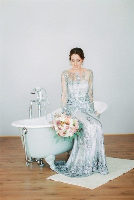 Chica con un vestido de novia de color verde sentada en una bañera