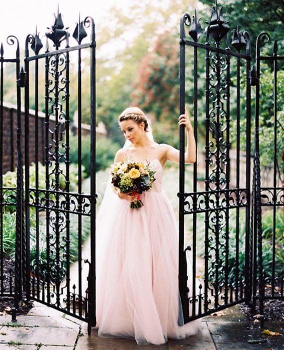 Chica vestida de novia usando un vestido de color rosa
