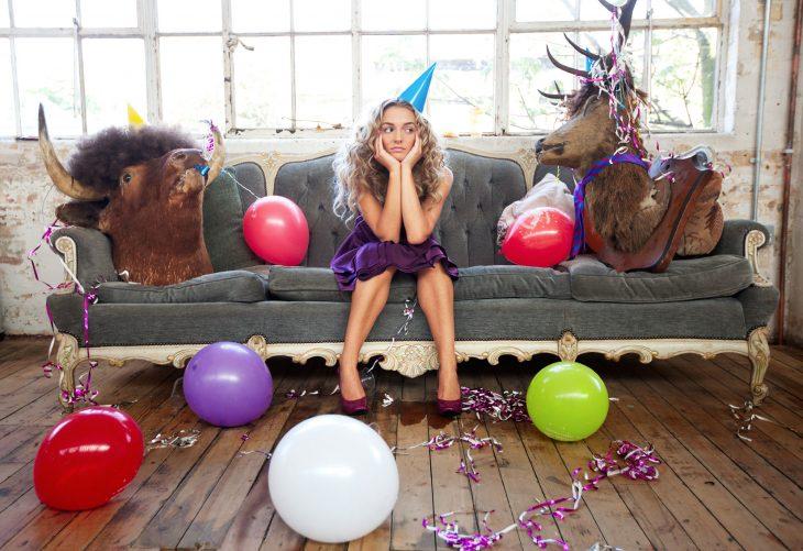 Chica sentada en un sofá con un gorro de fiesta aburrida