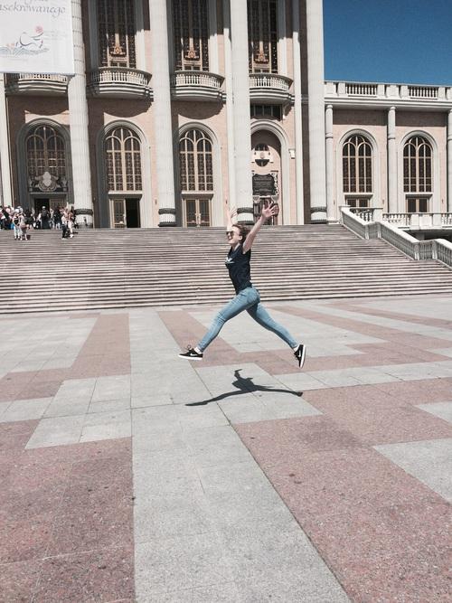 Chica corriendo y brincando frente a un edificio