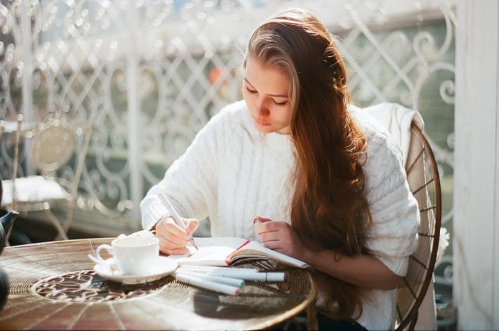 Chica escribiendo una carta mientras está sentada en una mesa