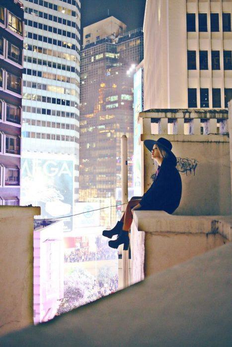 Chica sentada en una azotea viendo hacia la luna