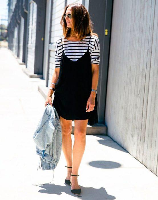 Chica caminando por la calle mientras usa un vestido negro largo con camisa debajo
