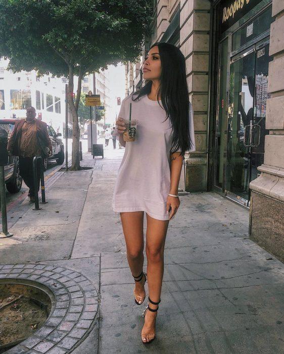Chica usando un vestido largo y caminando por la calle