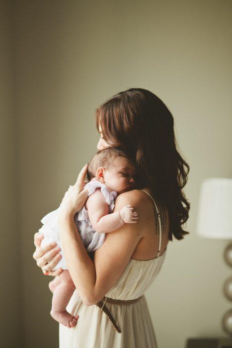 mujer sosteniendo a una bebé en brazos mientras está durmiendo