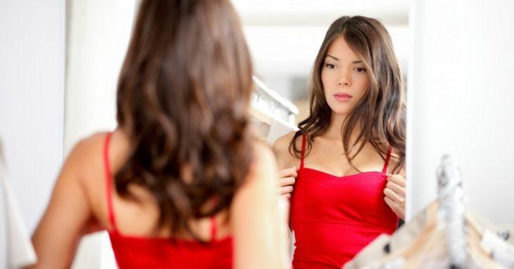 mujer con vestido rojo mirando su busto