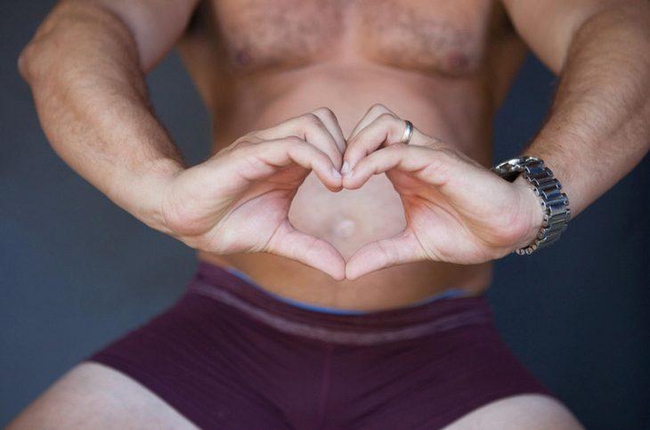 Hombre haciendo un corazón con las manos frente a su estomago