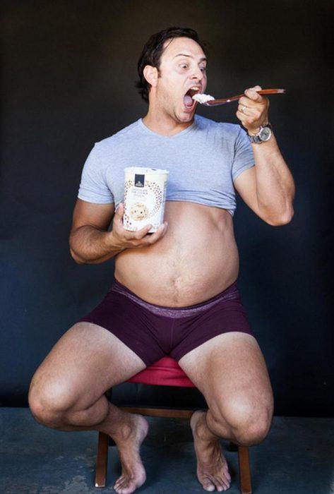 Hombre mostrando su barriga mientras come helado