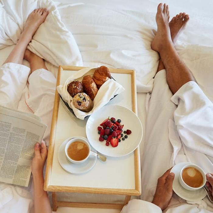 Charola de comida con pan y fruta colocada en una cama