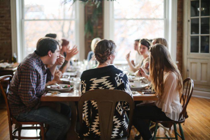 Personas sentadas en una mesa comiendo