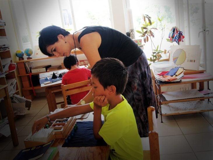 Guía Montessori trabajando con un estudiante