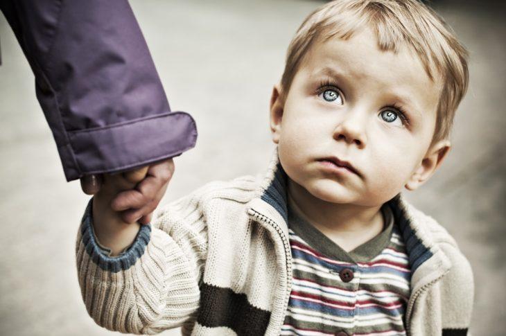 Niño toma la mano de uno de sus padres