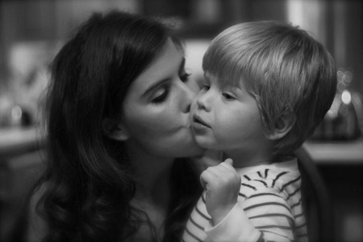 Mamá besa a su hijo en la mejilla