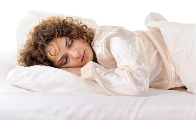 chica cabello rizado duerme sobre funda de satín