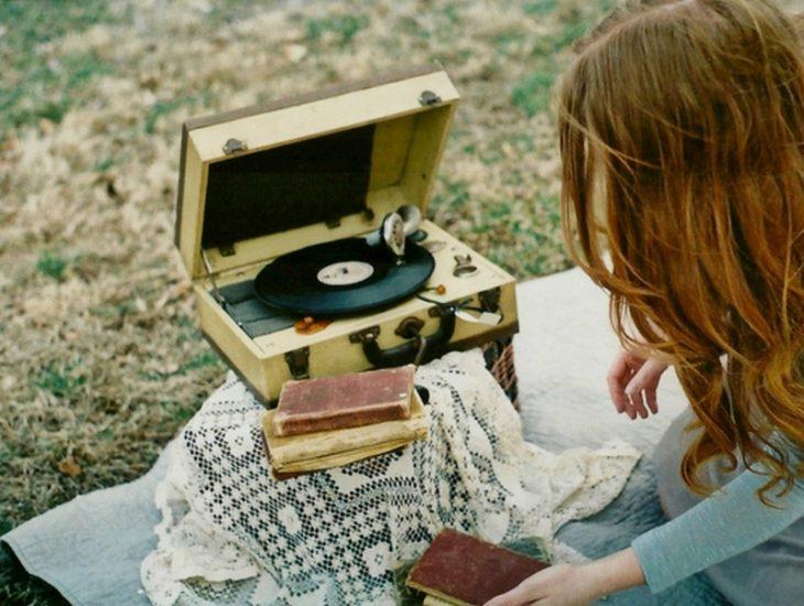 gif chica escuchando música y leyendo en campo