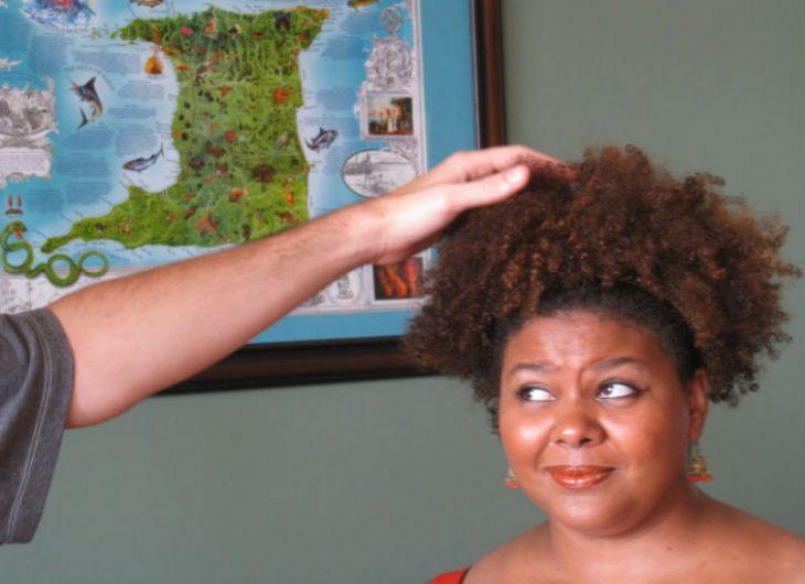 persona tocando el cabello de mujer con cabello rizado