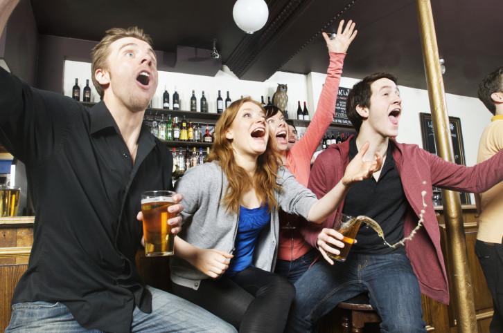 chicos viendo deportes en un bar
