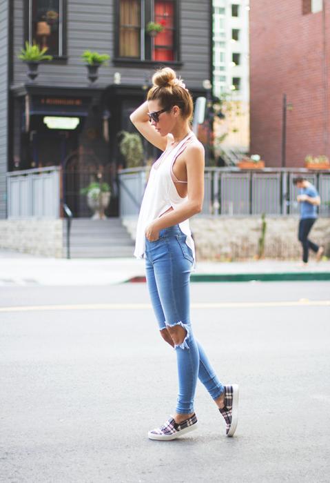 Chica caminando por la calle usando una blusa blanca y jeans