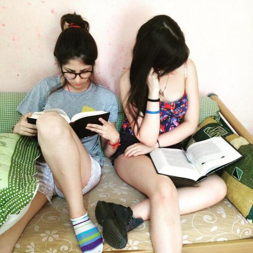 Hermanas sentadas en la cama leyendo libros