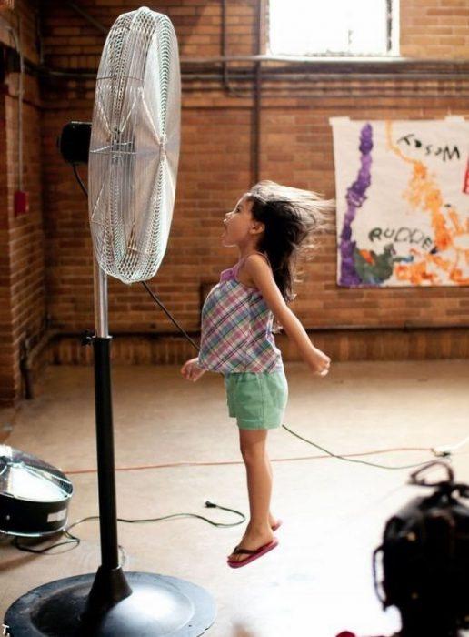 niña brincando frente al ventilador