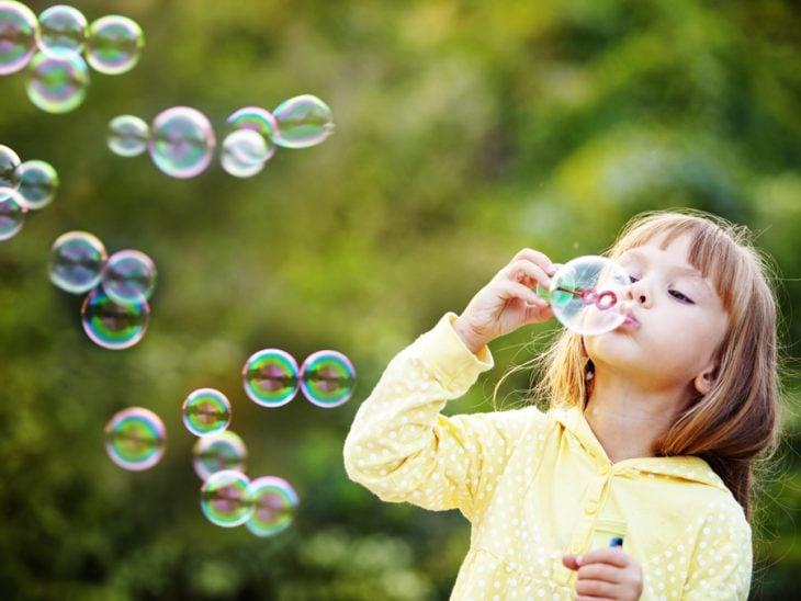 niña haciendo burbujas